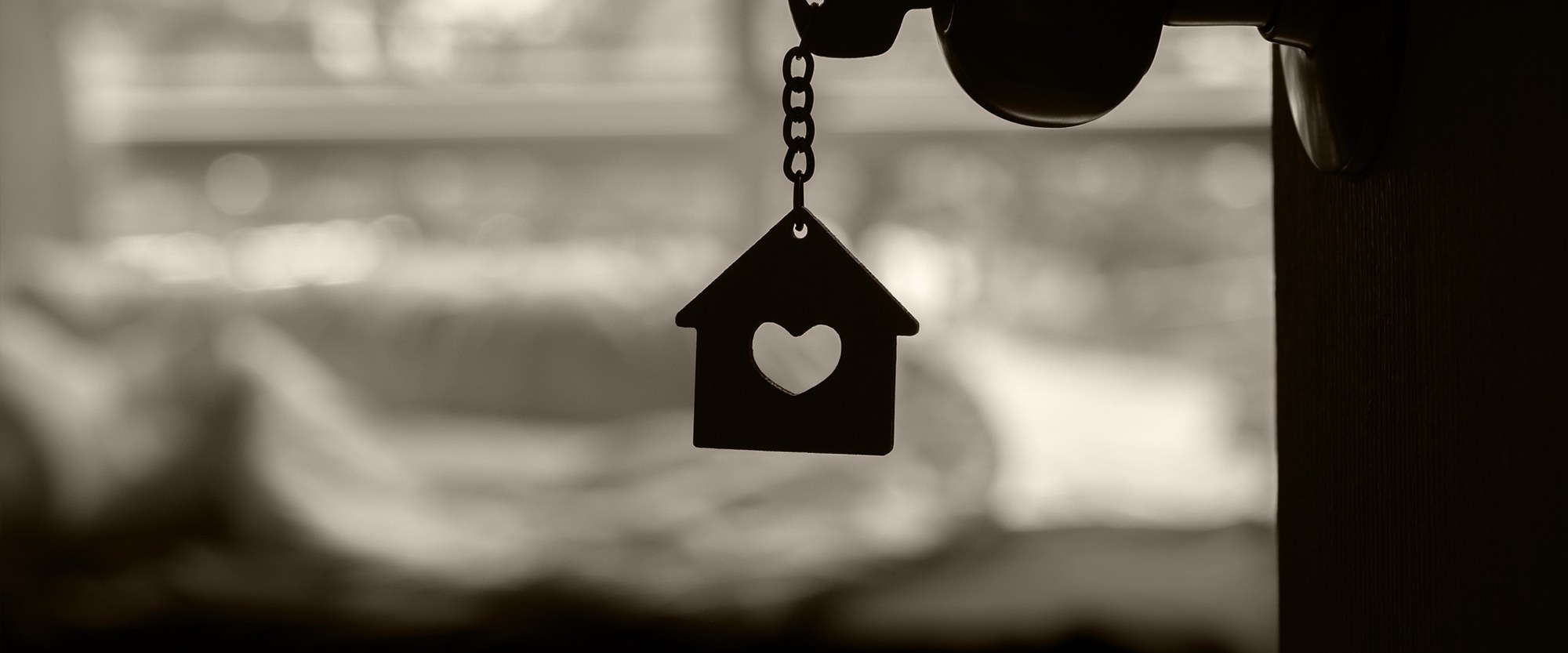 Key in door with a house with a heart keychain dangling