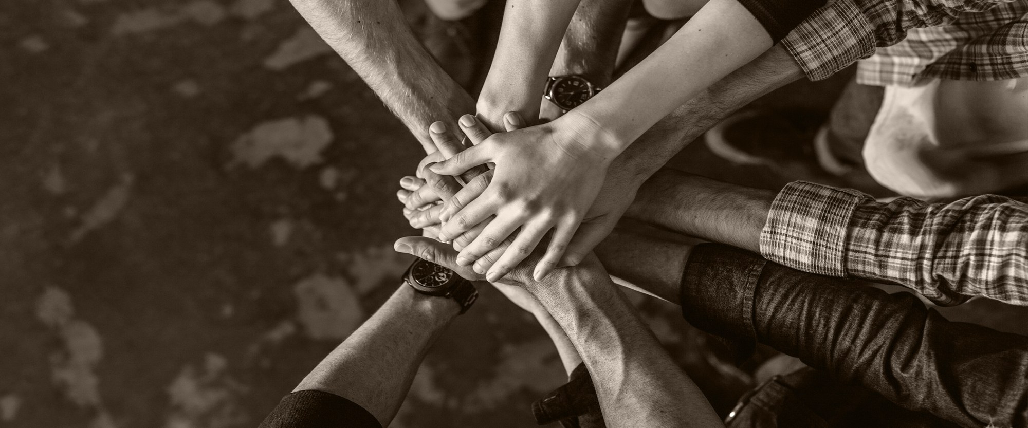 Group of people in circle with hands stacked together.