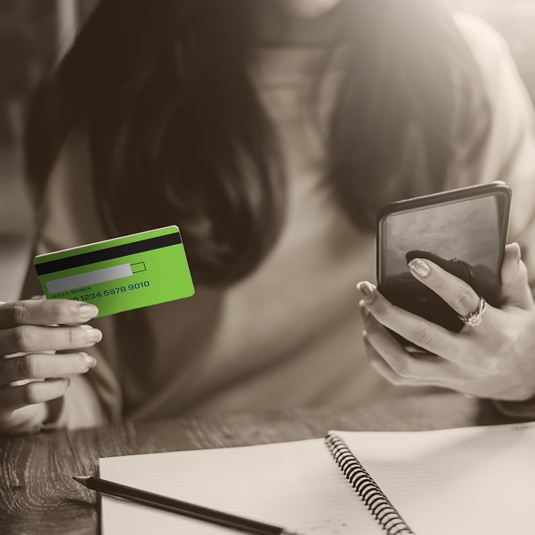 Woman at desk holding credit card and looking at phone